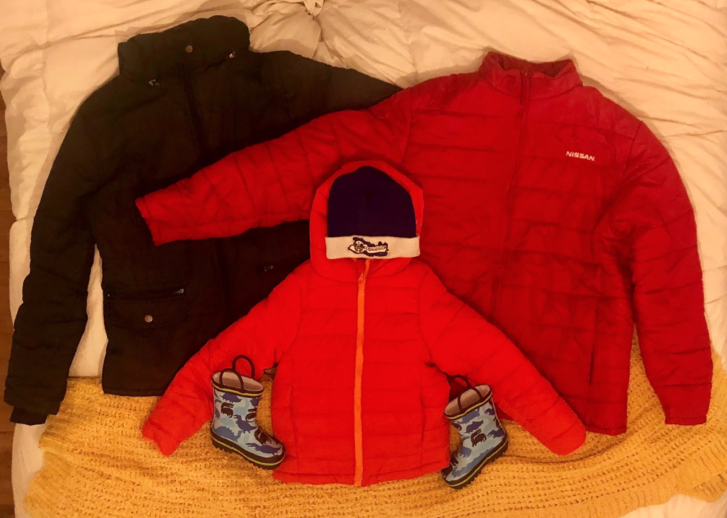 three winter jackets on a bed