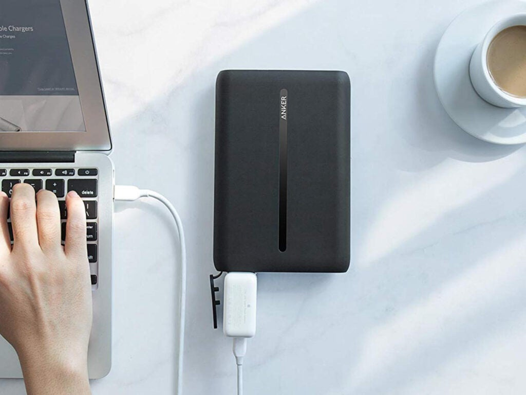 black portable laptop charger connected to laptop