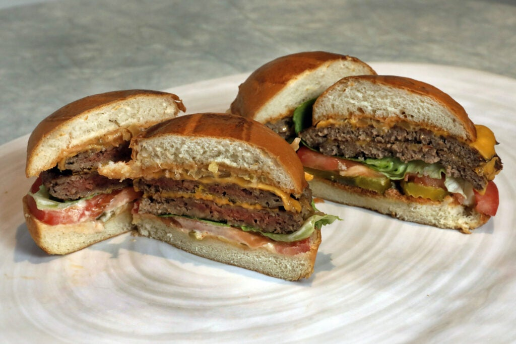 An Impossible Burger and hamburger cut in half