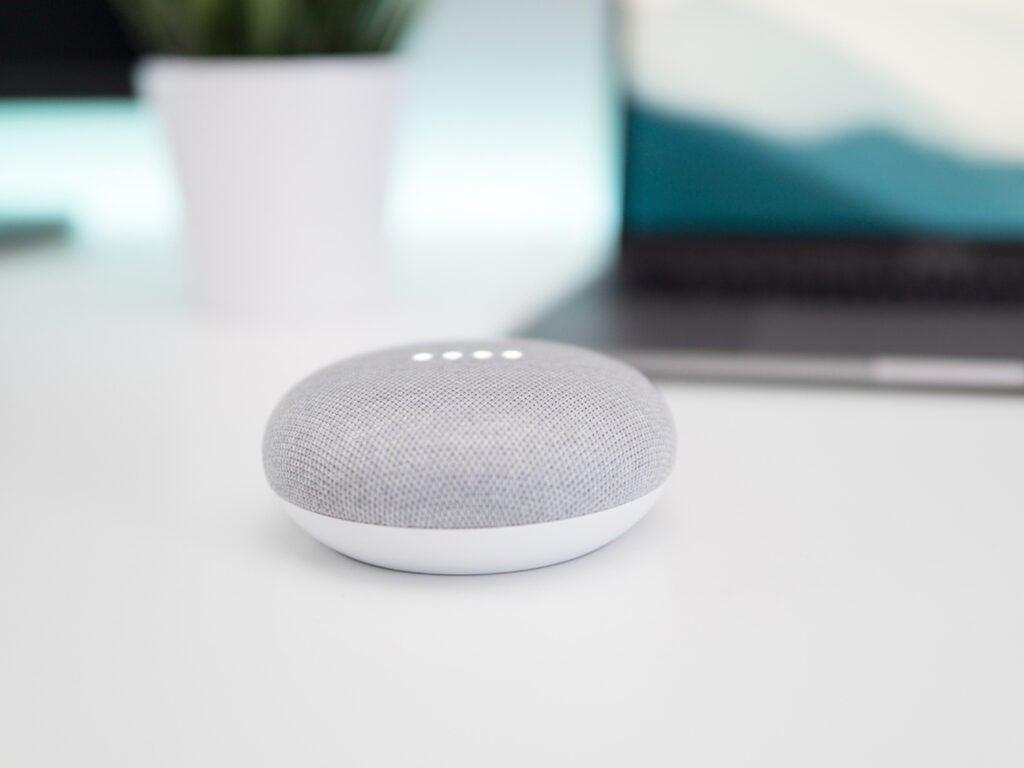google home mini over a white table