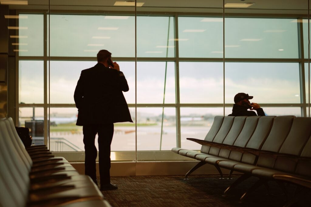 two people in an airport talking on phones