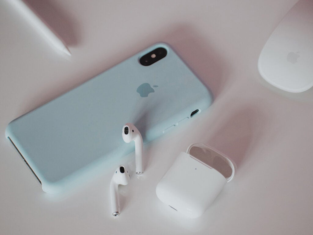 iphone and airpods laying on a white table