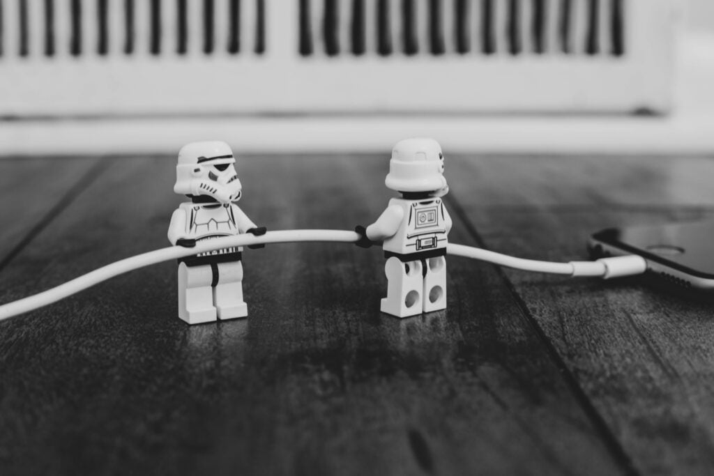 stormtrooper lego figurines pulling an iphone cable