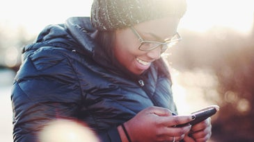 A person standing outside wearing a blue winter coat and a gray knit hat while smiling and looking at their phone.