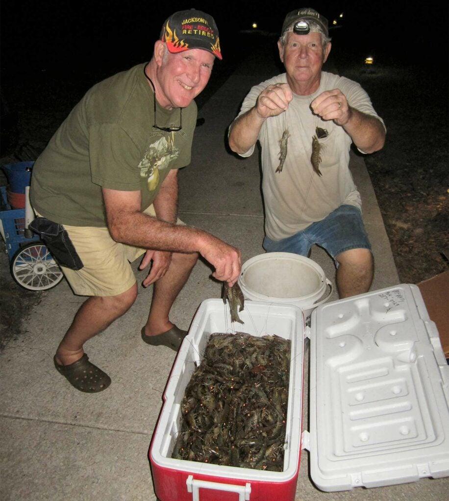 two men over a cooler of shrimp