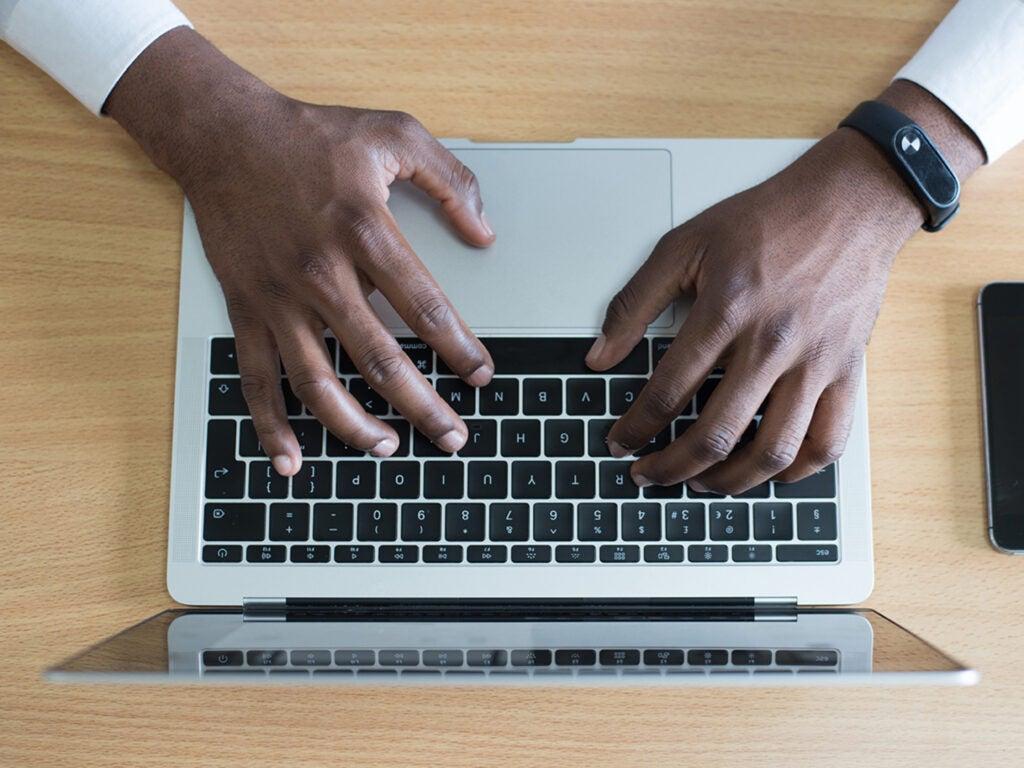hands on keyboard of laptop