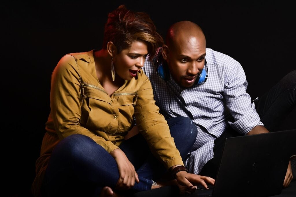 couple looking surprised at laptop