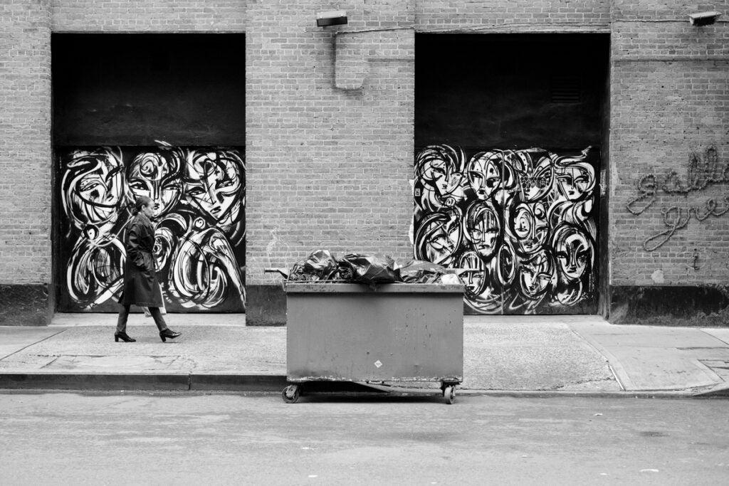 pedestrian against black and white mural
