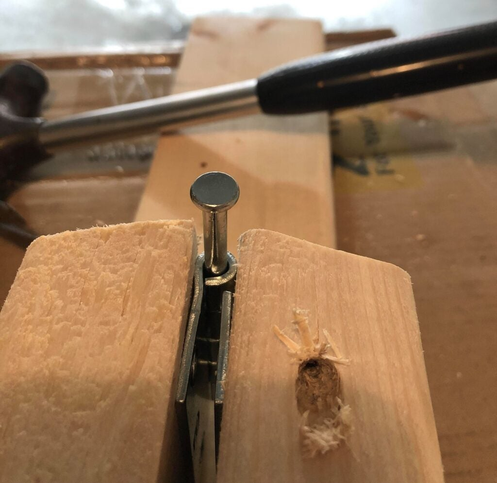 the pin in the hinge of a folding saw horse