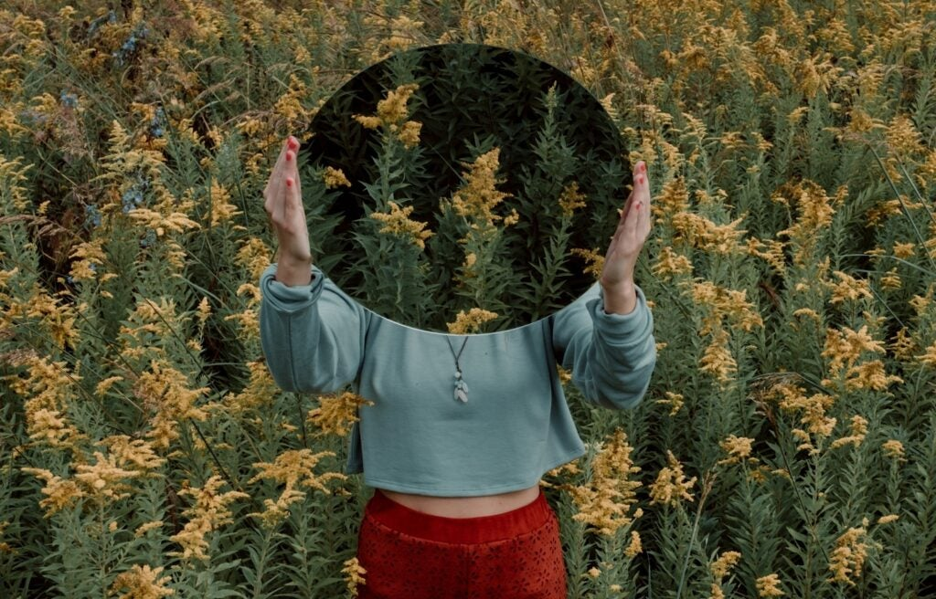 person holding a mirror in a meadow