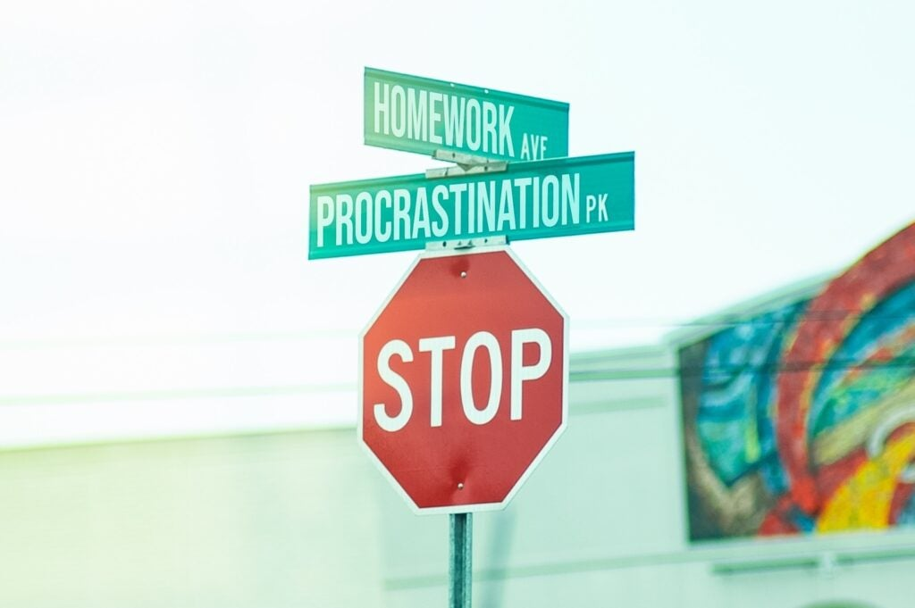 stop sign and street signs reading procrastination and homework