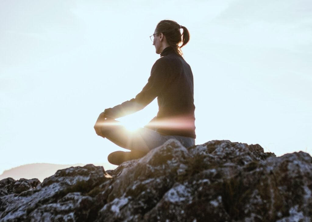 person meditating in a hill top