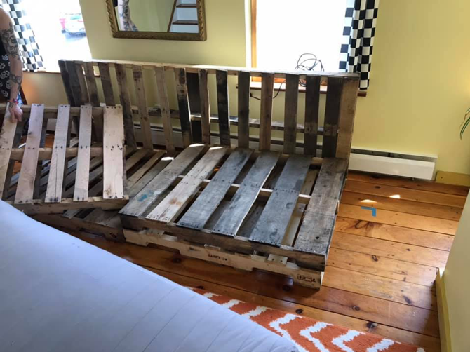 three wooden pallets in a living room that are about to become a couch