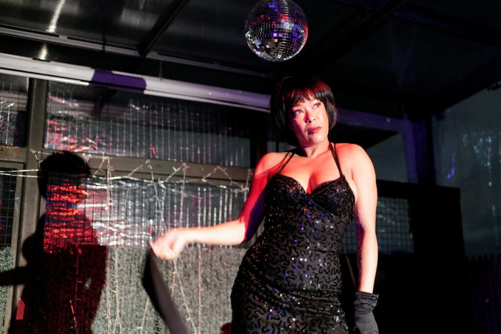 performer in black dress under disco ball