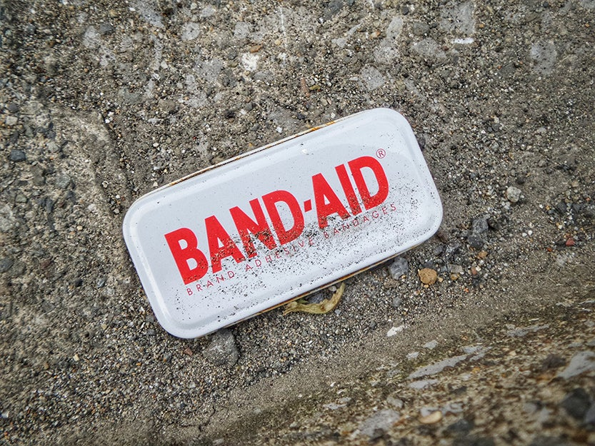 band-aid container on ground