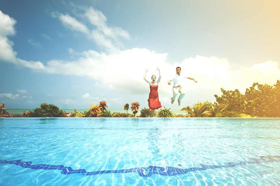 two people jumping into a pool