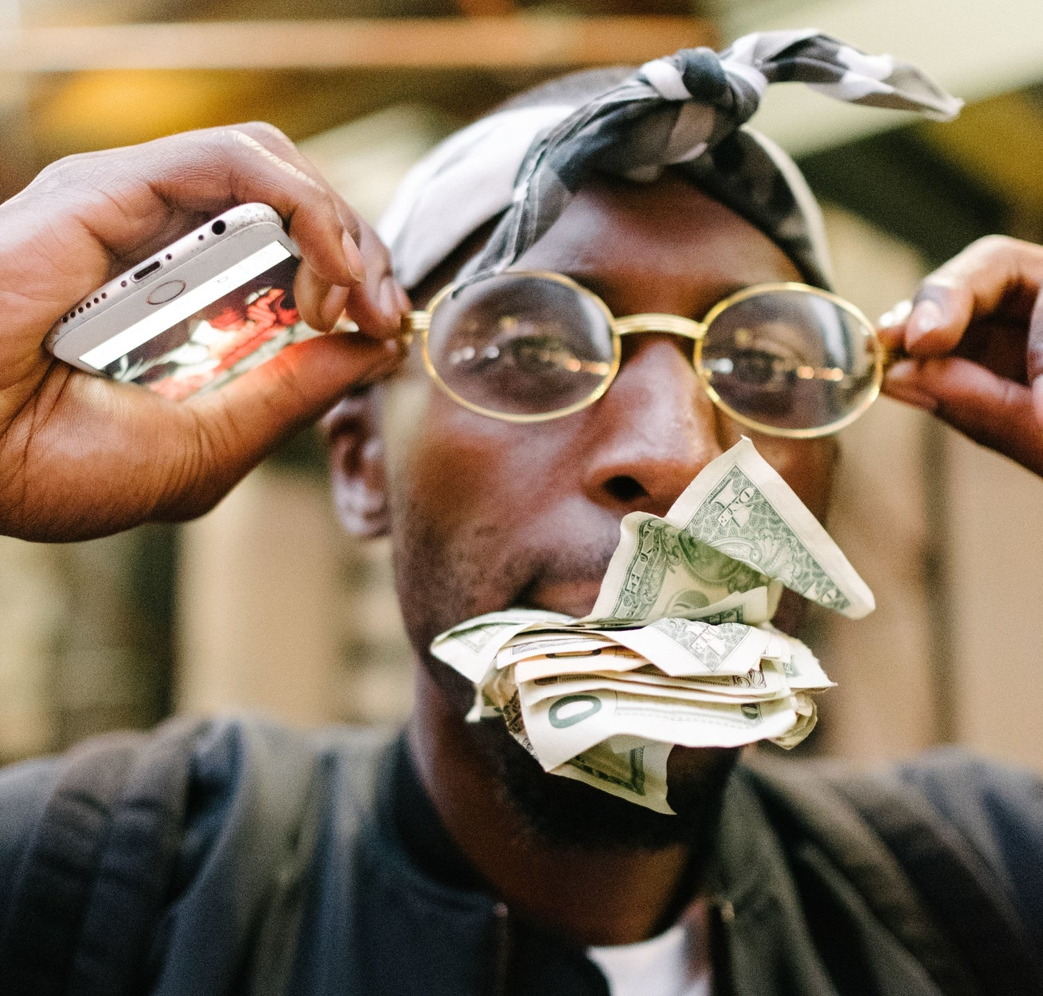 a man wearing sunglasses while holding cash money in his mouth