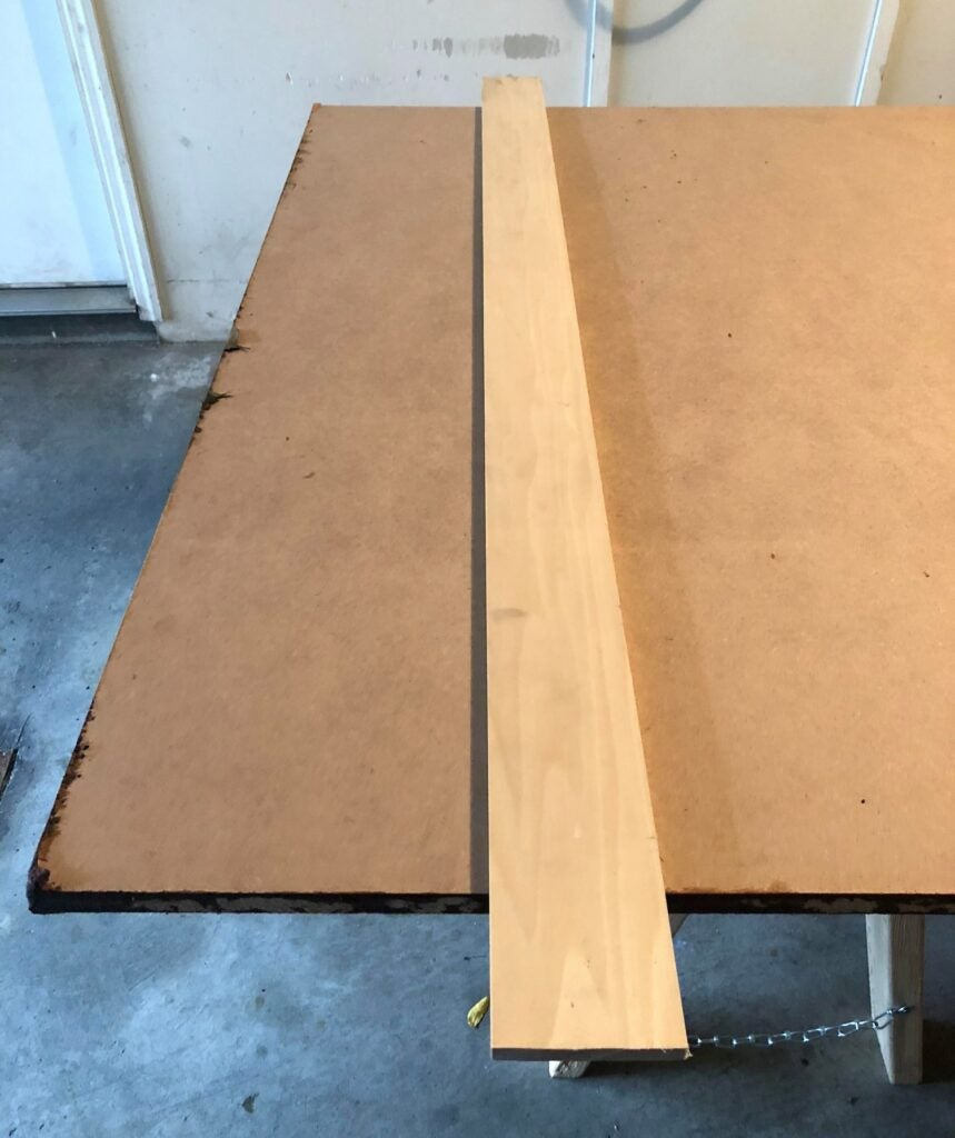 a piece of poplar on top of a sheet of MDF, being used as a straightedge