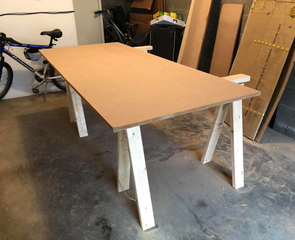 a sheet of MDF on top of two saw horses in a garage