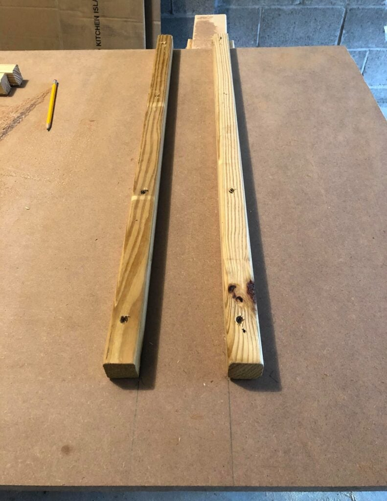 two pieces of 1-by-1 wood screwed to an MDF sheet to serve as brackets for saw horses to fit into