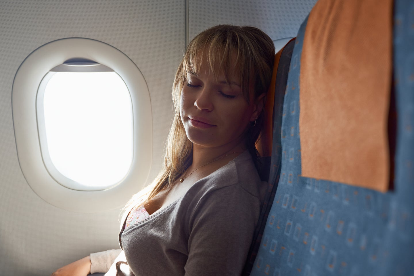 Person sleeping peacefully on an airplane.