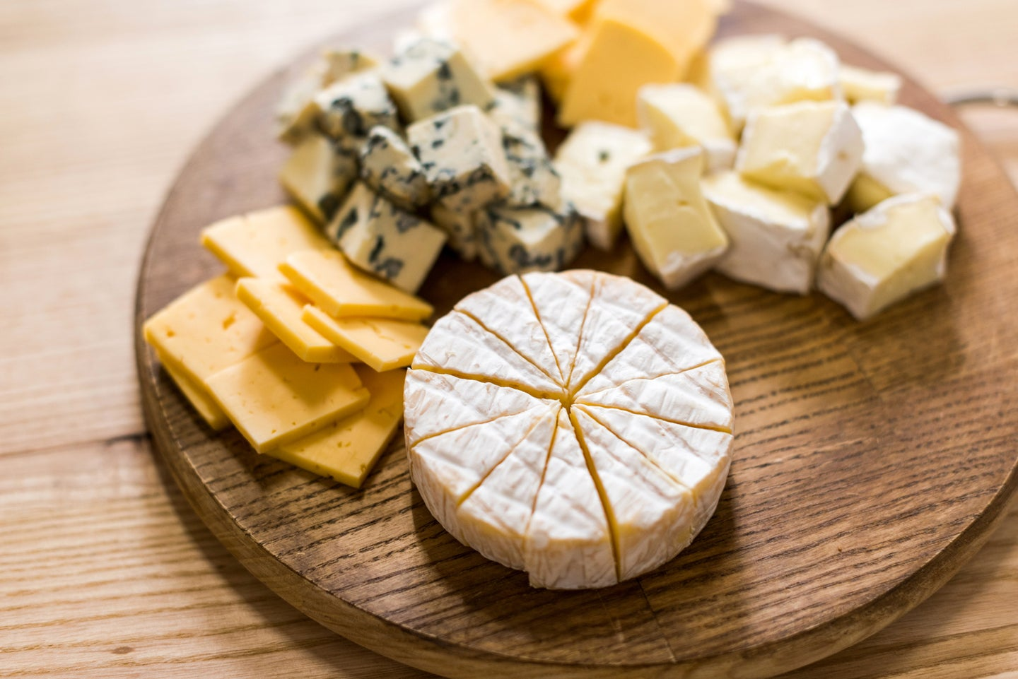 a cheese board with different cheeses of different shapes