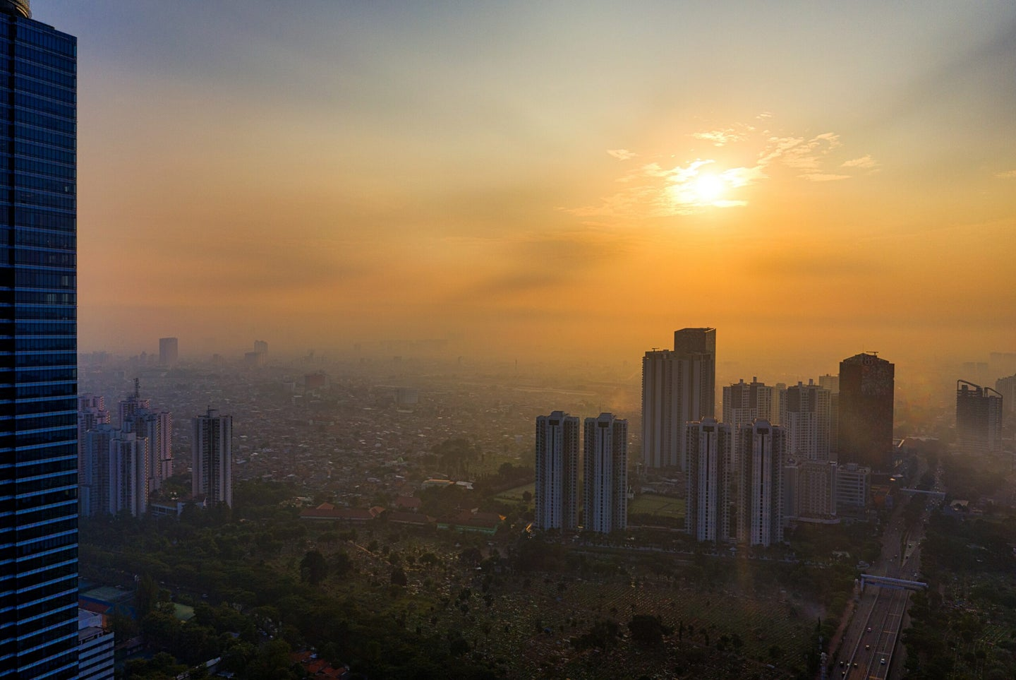 high risk buildings in Jakarta, Indonesia in front of golden sun