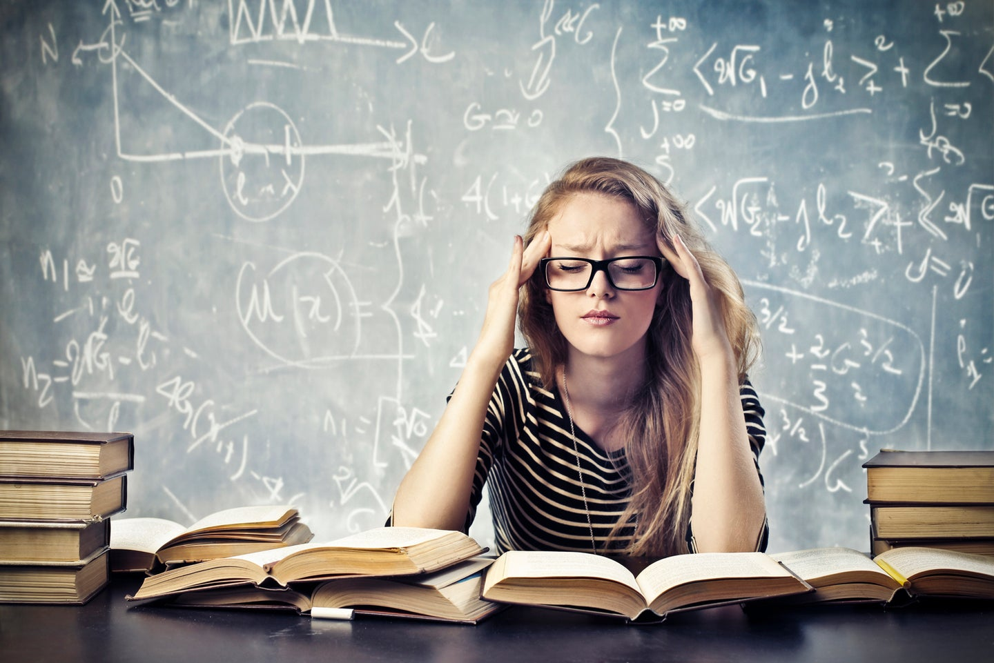 a blonde woman looking stressed out about math and surrounded by books