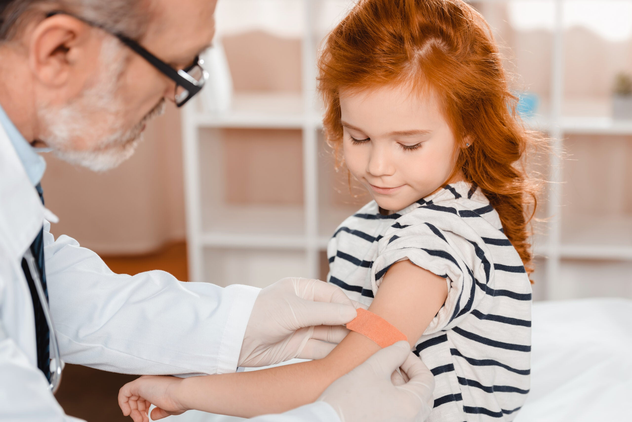 child getting a vaccine by her doctor