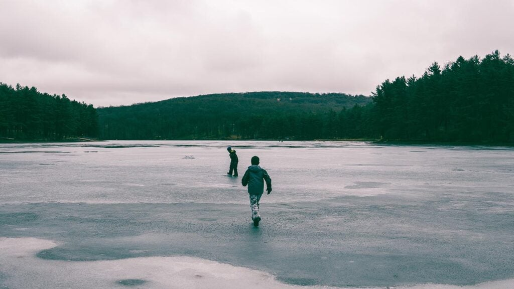Two kids running into a frozen lake