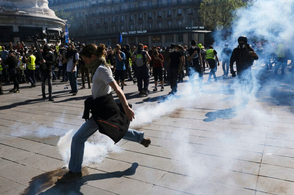 Person kicking teargas canister in Paris protests