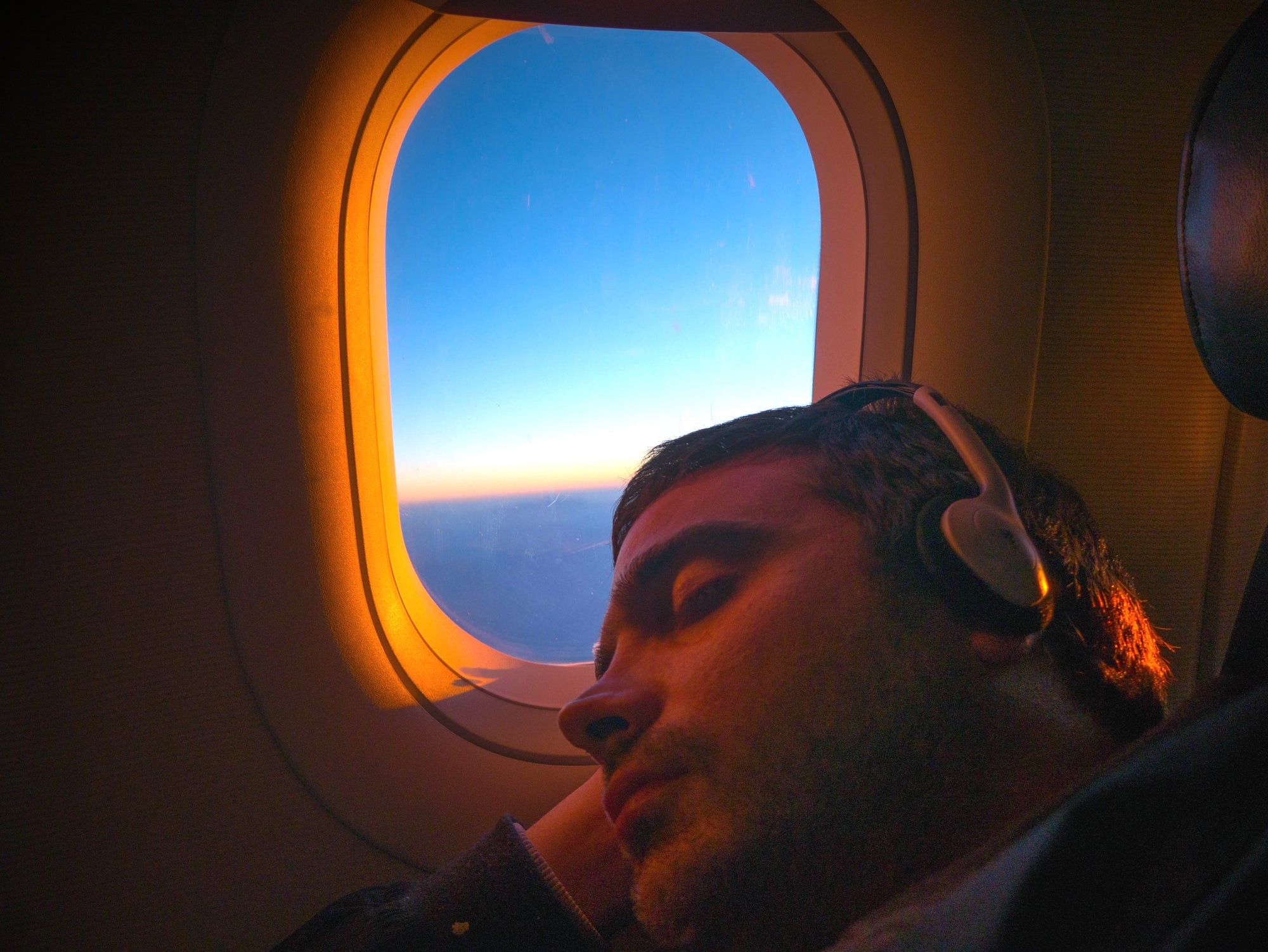 Person sleeping on plane with open window