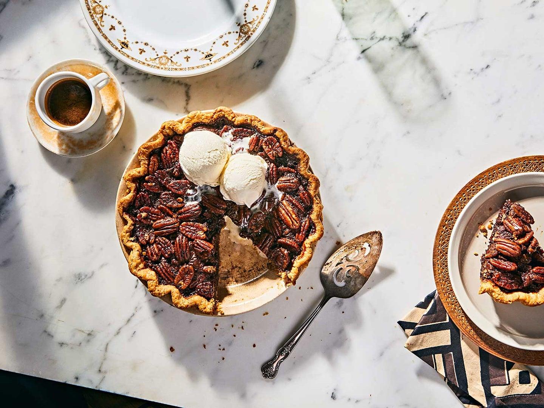 Bourbon Chocolate Pecan Pie served with vanilla ice cream on marble counter.