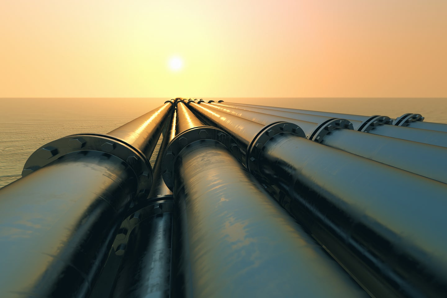 gas pipeline across snowy landscape at sunset