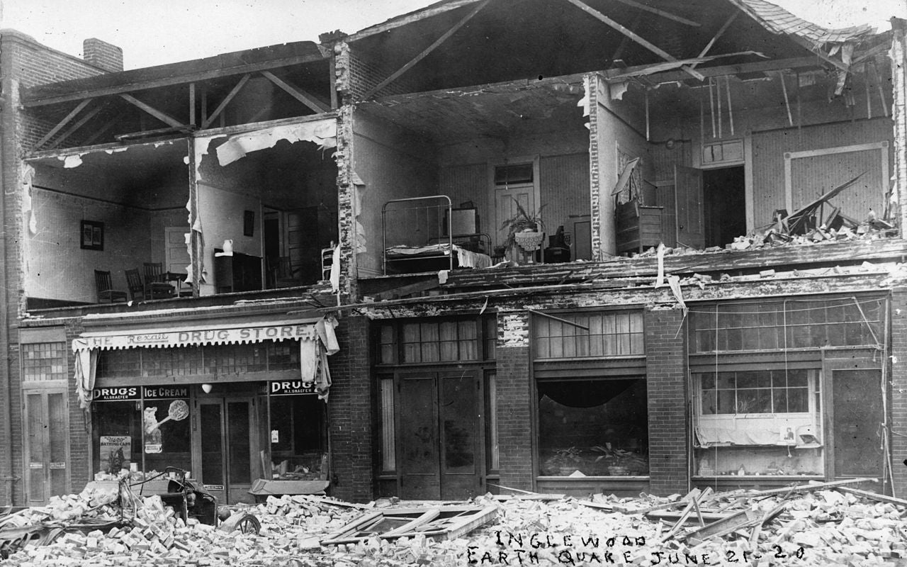 black and white photo of a row of damaged houses from an earthquake