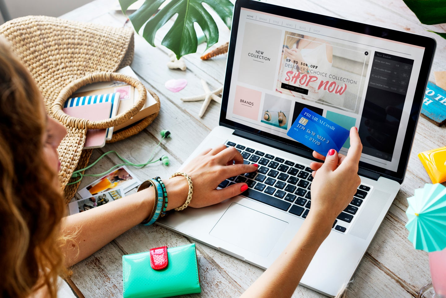 Person online shopping and holding credit card in front of computer on