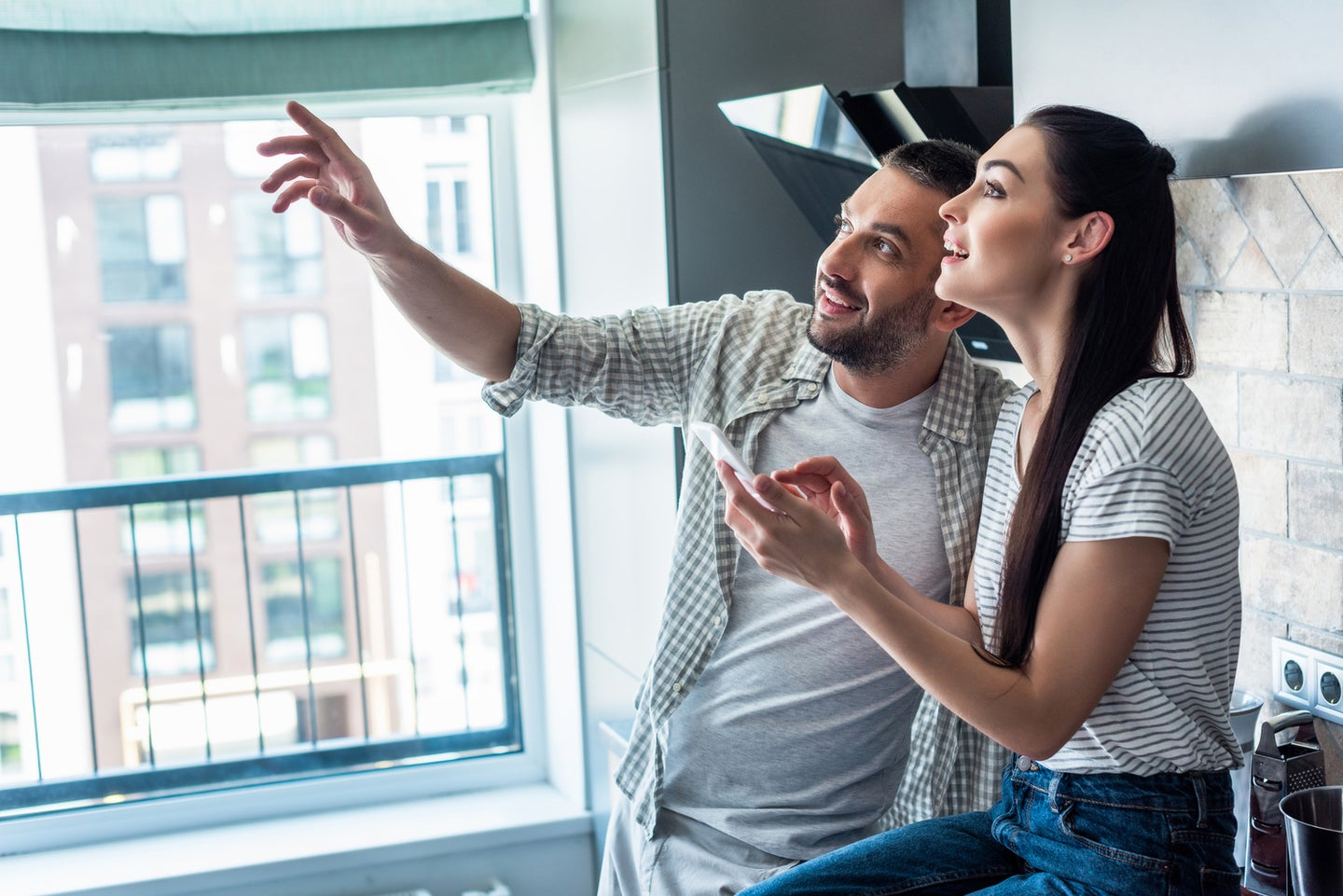 a man and a woman looking at something while pointing and using a phone