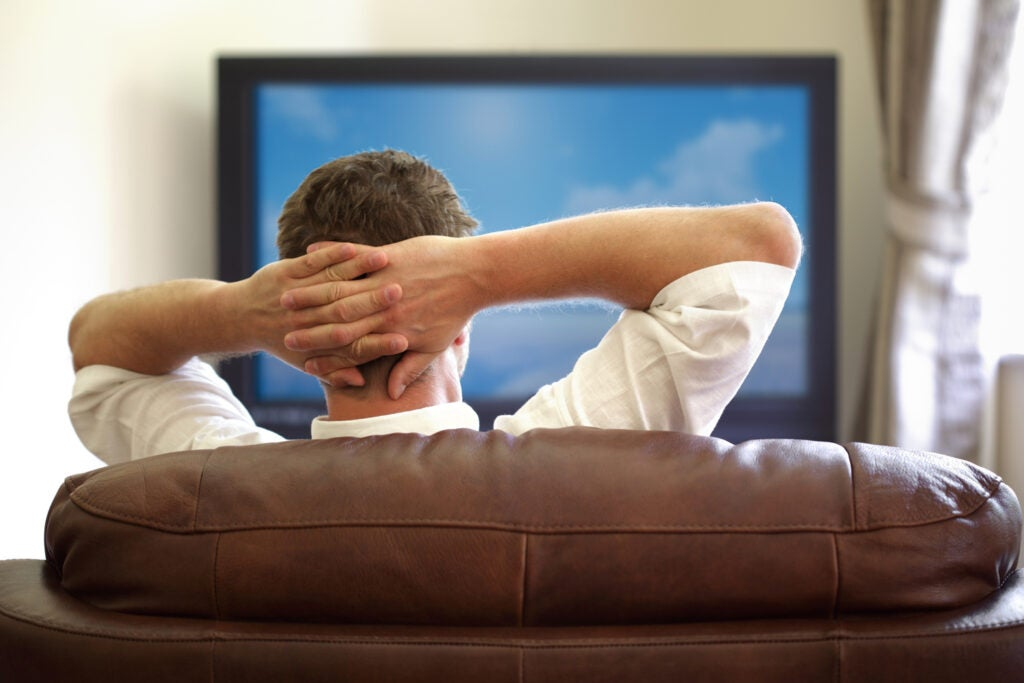 a man sitting on a leather couch watching TV