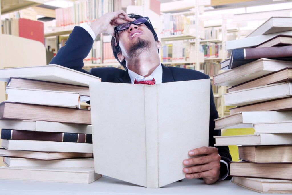 a stressed man in a suit and glasses trying to read a lot of books in a library