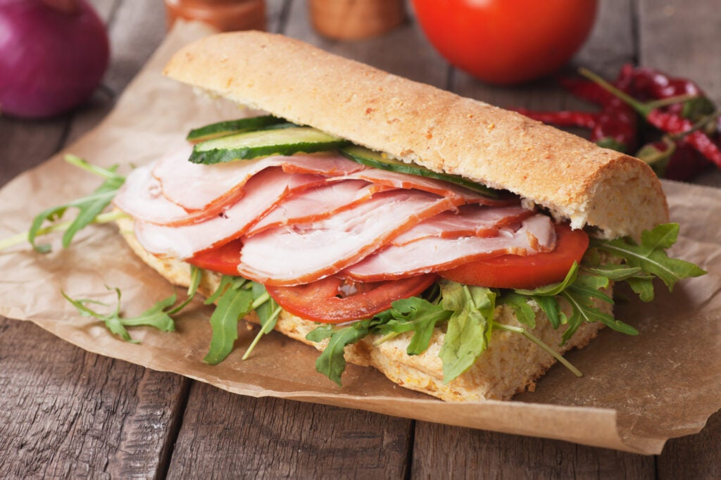 Submarine sandwich with smoked ham, tomato and rocket salad