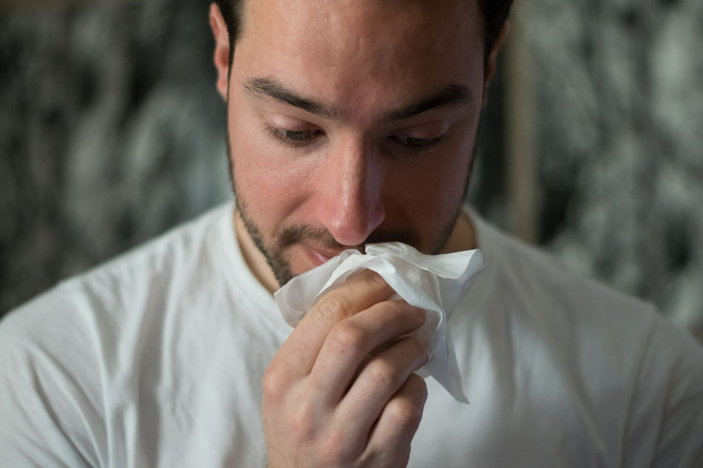 person holding tissue to nose