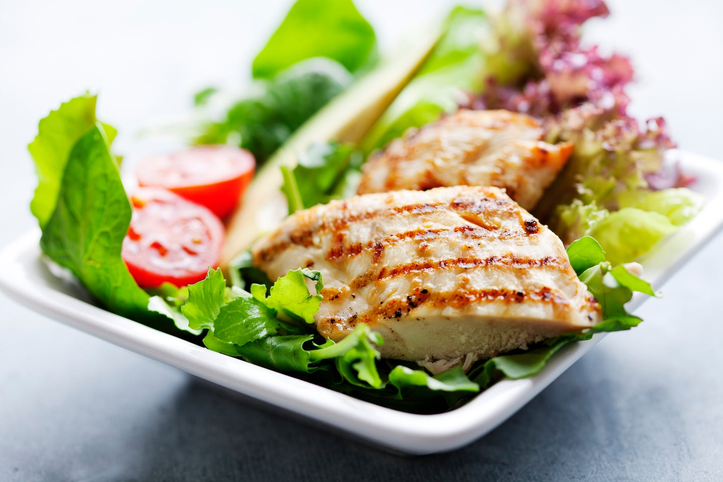 closeup of healthy salad with grilled chicken fillet, selection of lettuce, tomatoes and avocado,