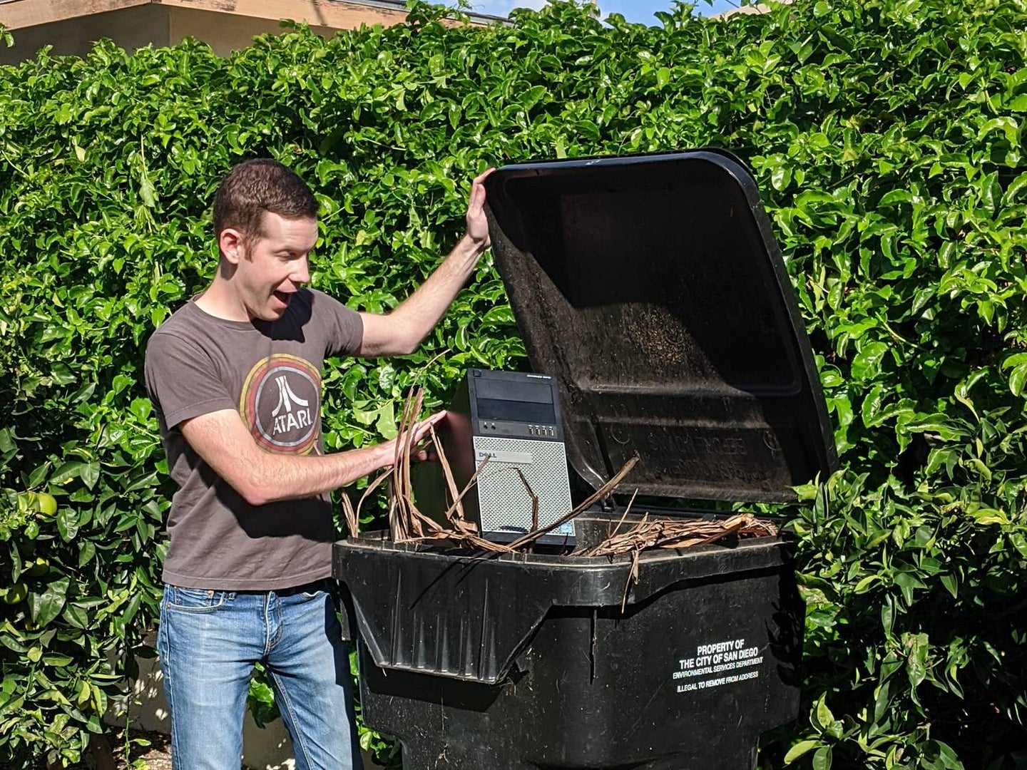 Man opening a trash can.