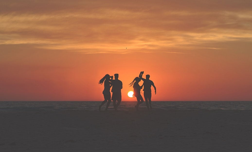people dancing on the beach during sunset