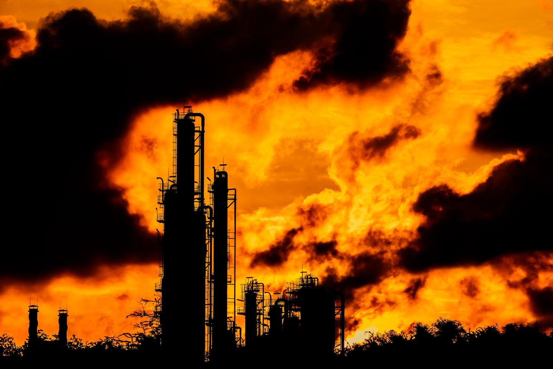 a power plant spews smoke into an orange sky