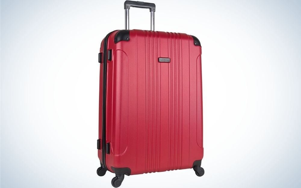Red luggage with 4 wheel spinners with top black grab handle standing upright from front.