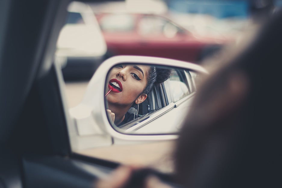 woman putting lipstick on in a car