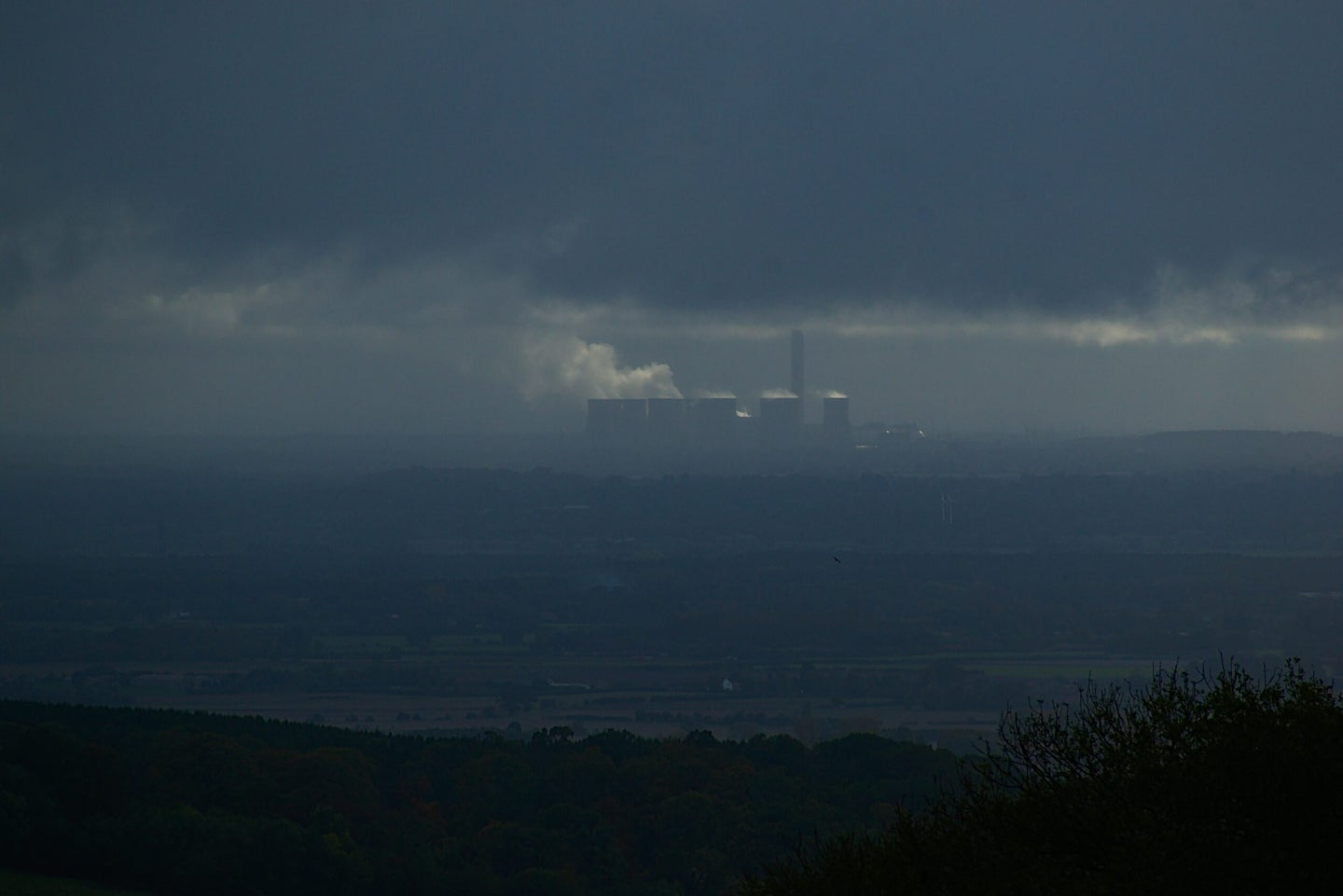landscape filled with smog with industrial building in the distance