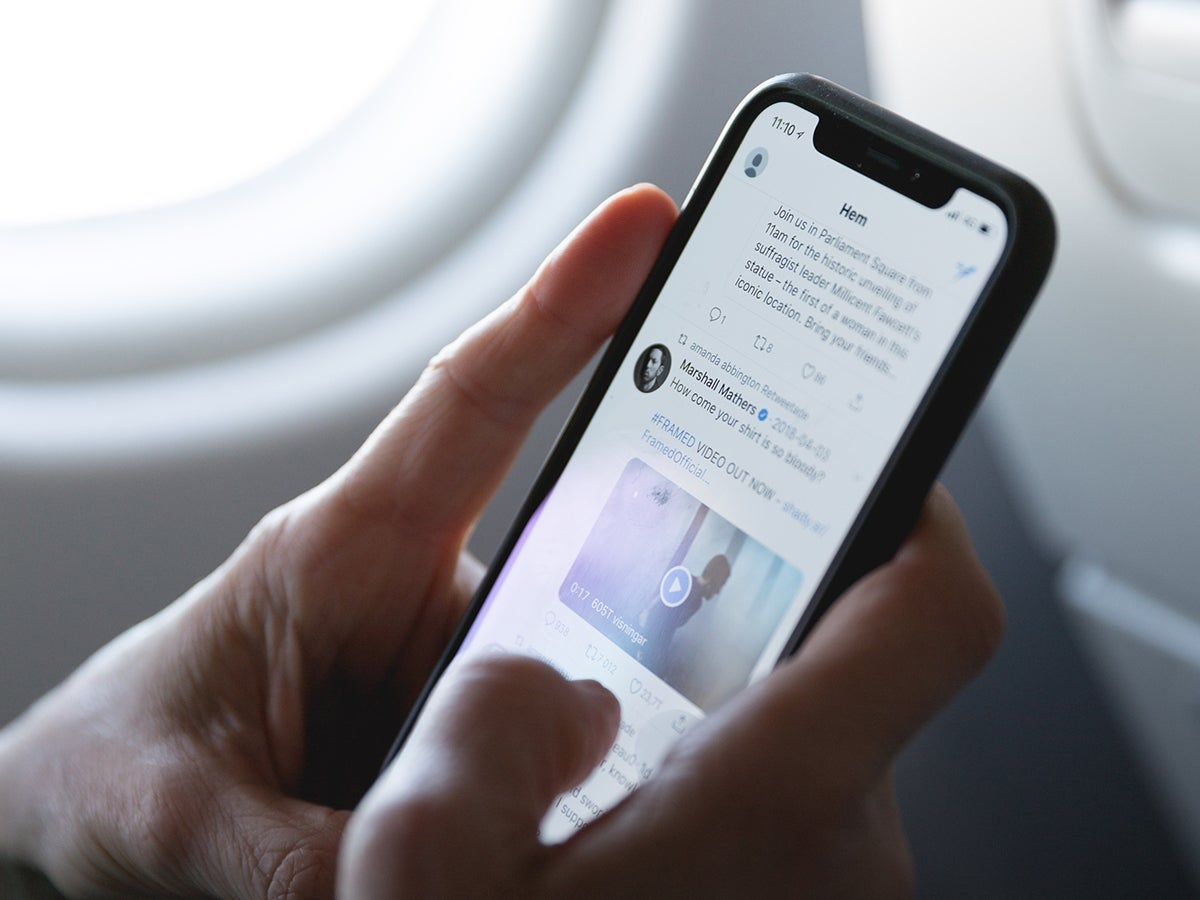 a person looking through their Twitter timeline on a phone while on an airplane