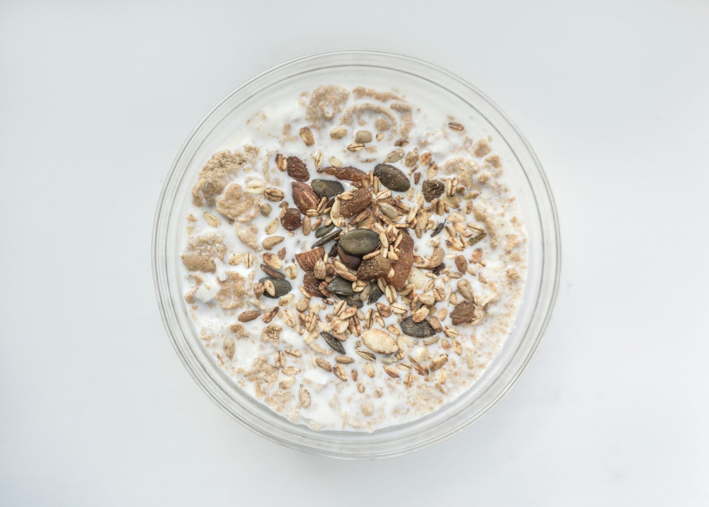 bowl of oatmeal with milk on a white background
